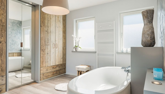 Heated wooden floors, wooden cabinetry and large mirrors complete this transitional style bathroom