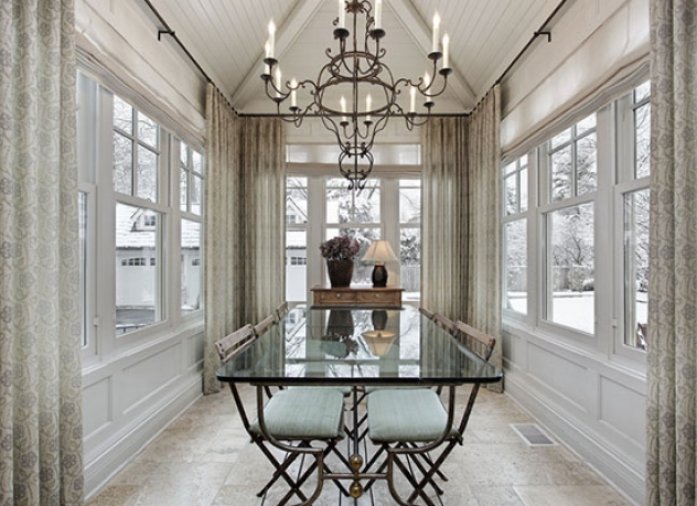 Sun filled dining room completed with rustic chandelier and glass table top