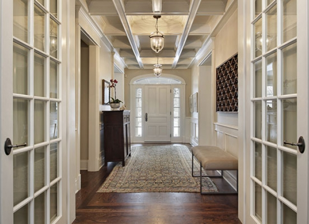 Beautiful corridor with ornate french doors leading into a classic hall.