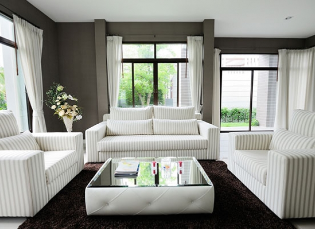 Pin striped couch used with light drapes and contrasting dark walls.