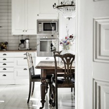 kitchen designed with old school table, chairs and light fittings against a moden kitchen design