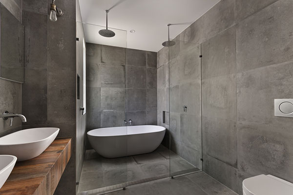 Grey effect block walls including double shower head and tub in wet room setting.